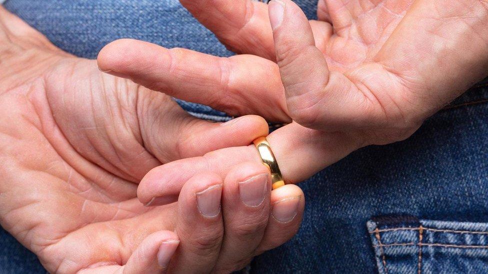 Hombre quitándose anillo de casado.