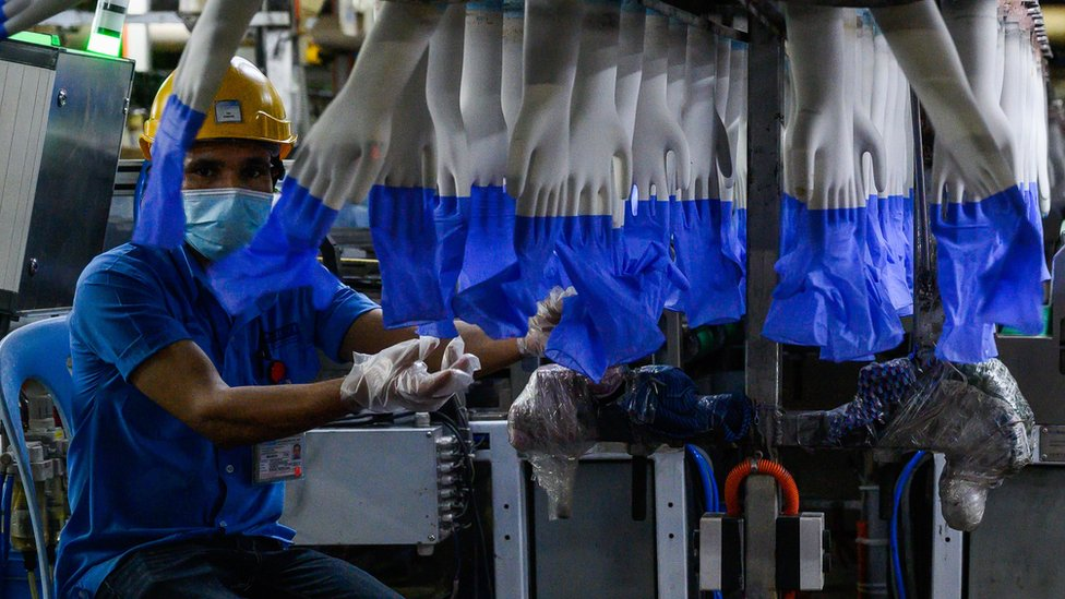 A worker inspects disposable gloves at a Top Glove factory in August