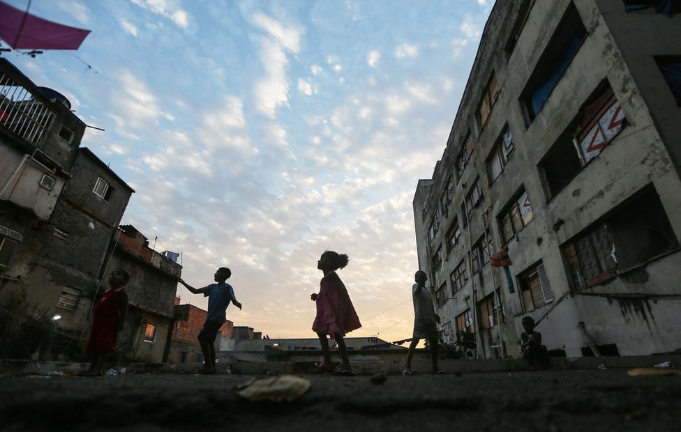 Youngsters fly kids outside an occupied building in the Mangueira 'favela' community on 9 August, 2016