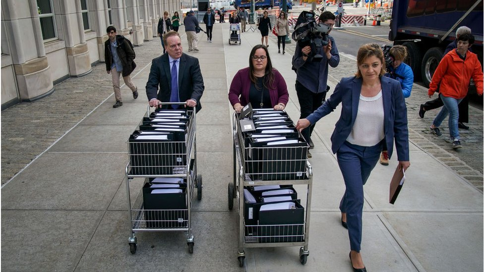 Staff and members of the prosecution team push carts full of court documents related to the U.S. v. Keith Raniere case as they arrive at the U.S. District Court for the Eastern District of New York