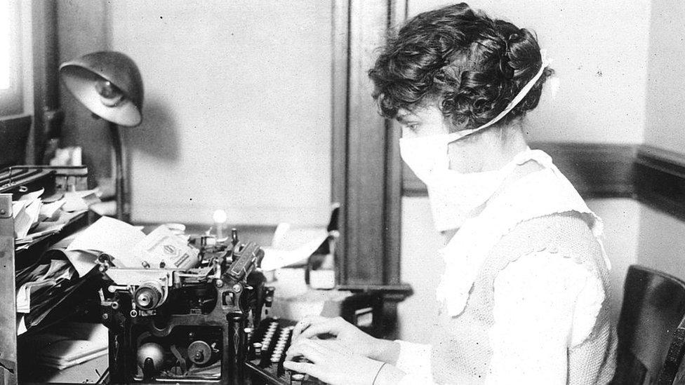 Una secretaria con mascarilla escribe a máquina en su escritorio en 1918