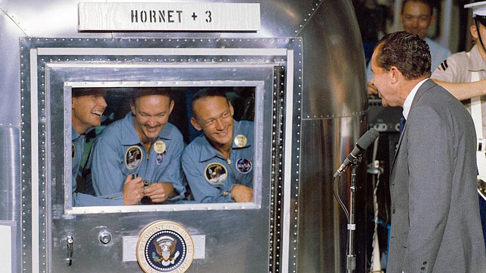 Nixon le da la bienvenida a los astronautas -confinados a la instalación de cuarentena móvil- tras la histórica misión de aterrizaje lunar del Apolo 11.