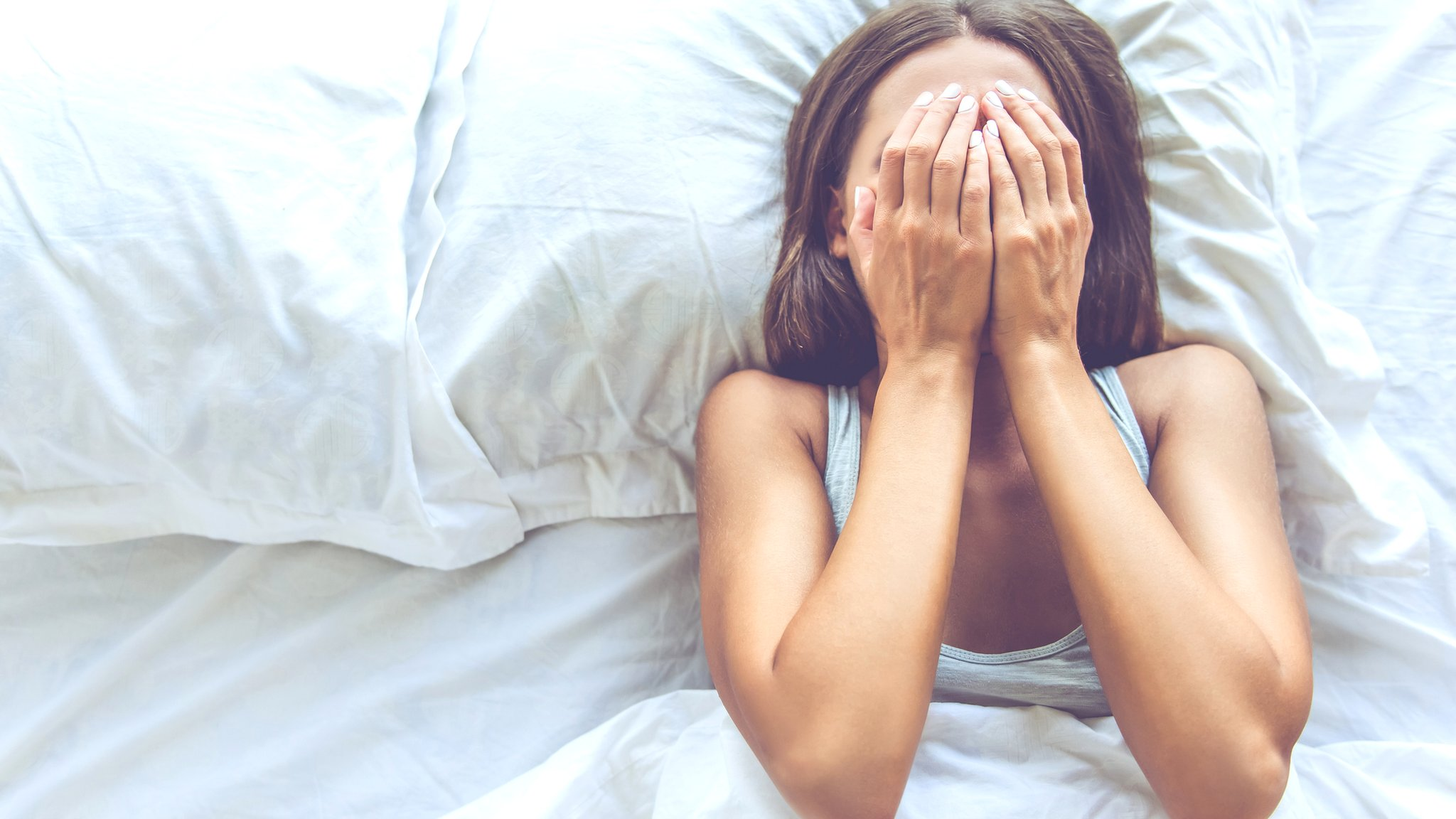 Young woman in bed trying to sleep