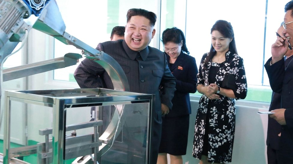 Kim Jong Un smiles toward electronic device in newly renovated facility with senior officials and his wife in the background