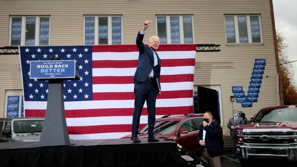 US Democratic presidential candidate Joe Biden raises his arm during a drive-in campaign event in Toledo, Ohio on 12 October 2020