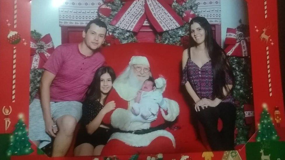 Família de Gabriel e Ana Cláudia posa em cenário natalino junto com Papai Noel, que segura a recém-nascida em seus braços