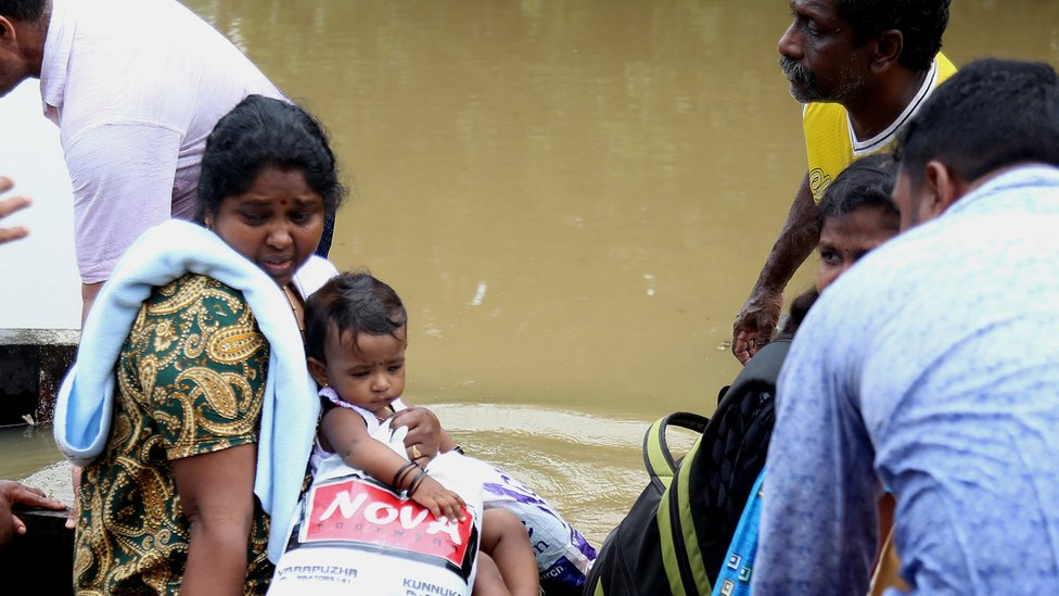 People take a boat to safety in Kochi