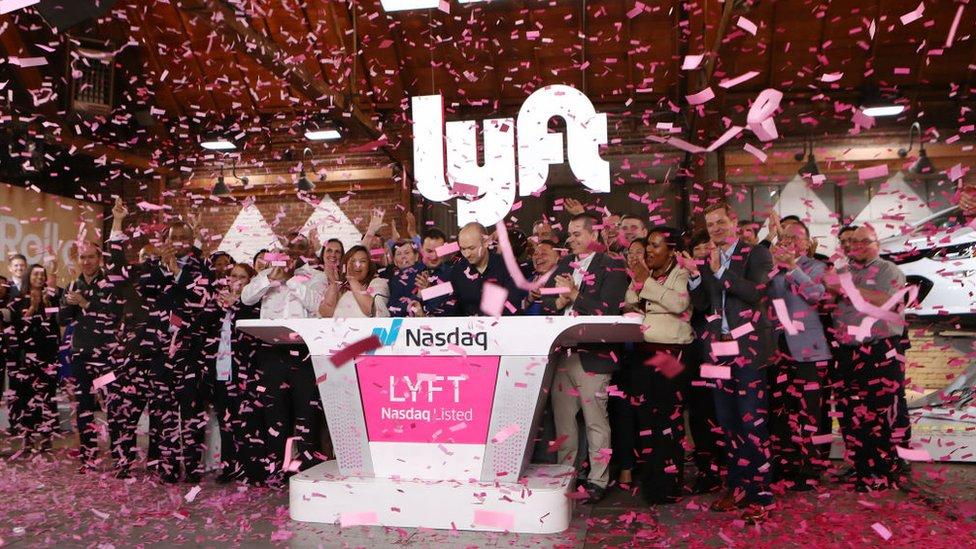 El CEO de Lyft en el centro tocando la campana de apertura de Nasdaq para celebrar la salida a la bolsa de la empresa.