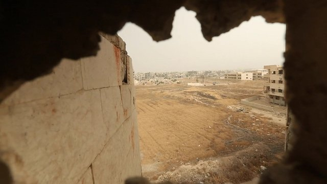 Camera looking through hole in wall to buildings outside