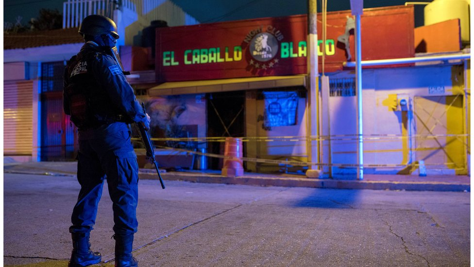 A police officer guards in the early hours in front of the El Caballo Blanco bar, attacked the previous night by an armed group, in Coatzacoalcos, in the state of Veracruz, Mexico, 28 August 2019