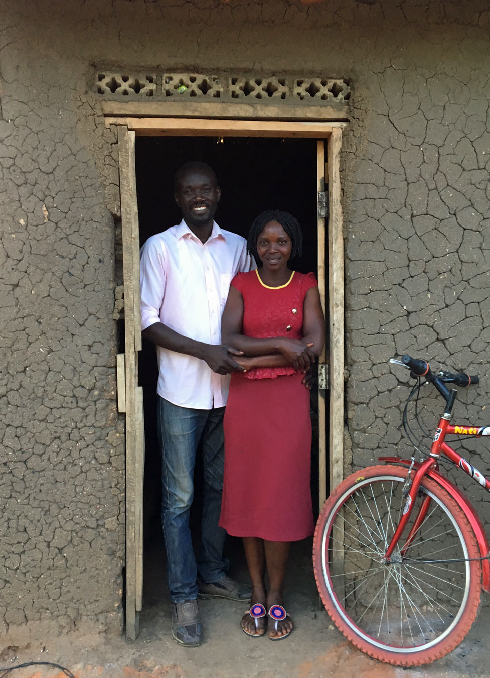 Herbat and Lucy standing in front of their house at Bidi Bidi