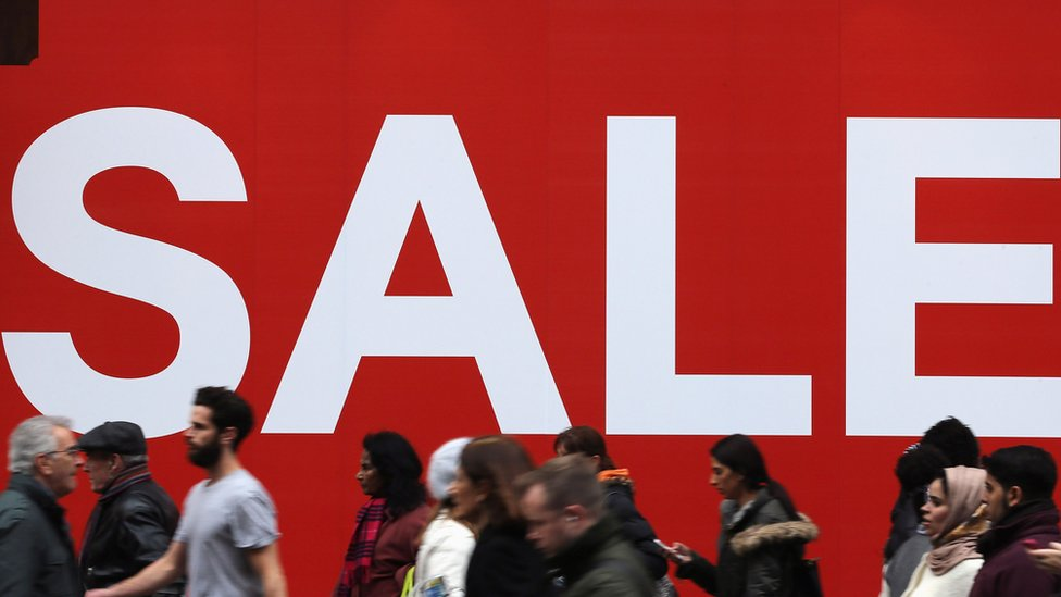 Large Sale sign in the window of a shop as people walk past outside