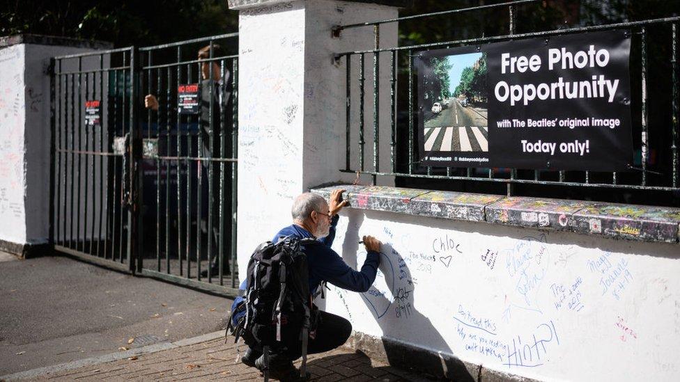 Un hombre escribe en el muro de los estudios de Abbey Road, en Londres