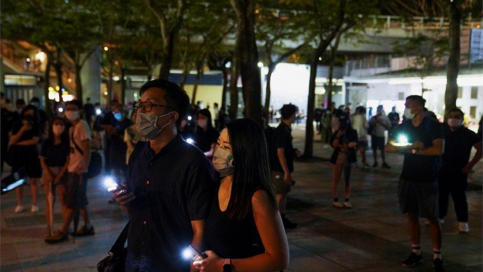 Personas con la luz de sus celulares encendidos cerca del parque Victoria de Hong Kong.