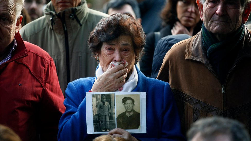 Carmen Benito Alcantarilla holds a picture of her uncle Valentin Alcantarilla Mercado during the exhumation of graves in Guadalajara's cemetery, Spain, 30 January 2016