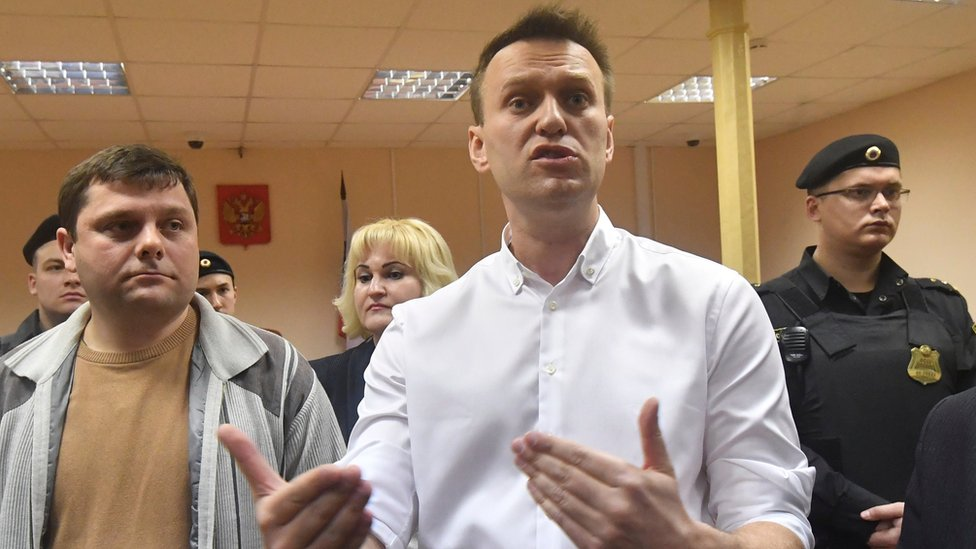 Russian opposition leader Alexei Navalny, right, and his former colleague Pyotr Ofitserov, left, speak to journalists in the court in Kirov, Russia, Wednesday, Feb. 8, 2017