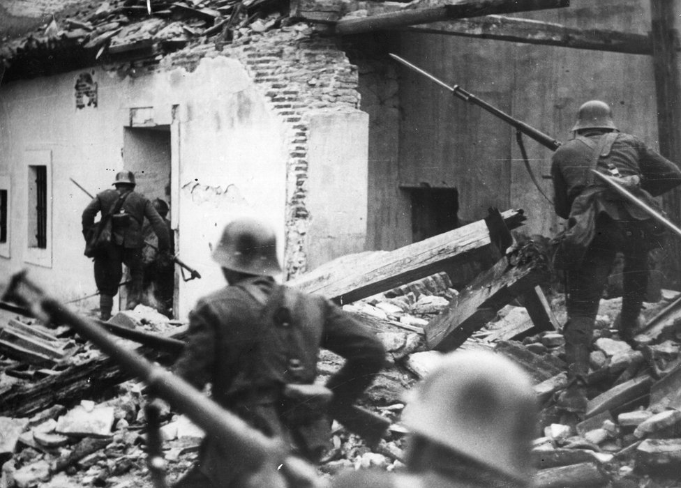 Nationalist troops loyal to General Franco advance, bayonets fixed, through the debris of houses in Madrid wrecked in air raids during the Spanish Civil War