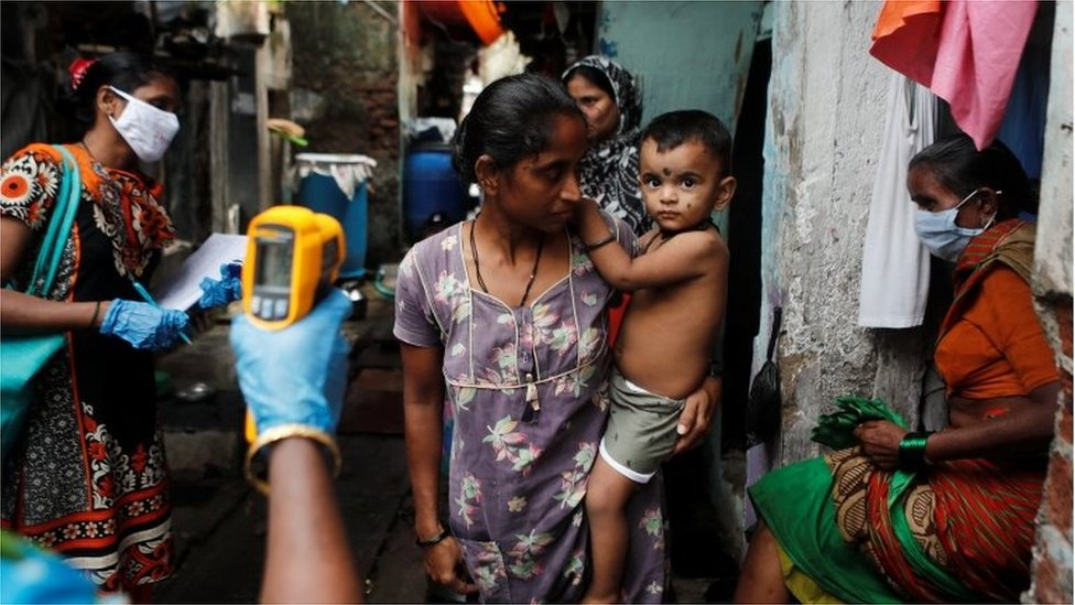 A healthcare worker checks the temperature of a woman in Mumbai, India, July 6, 2020