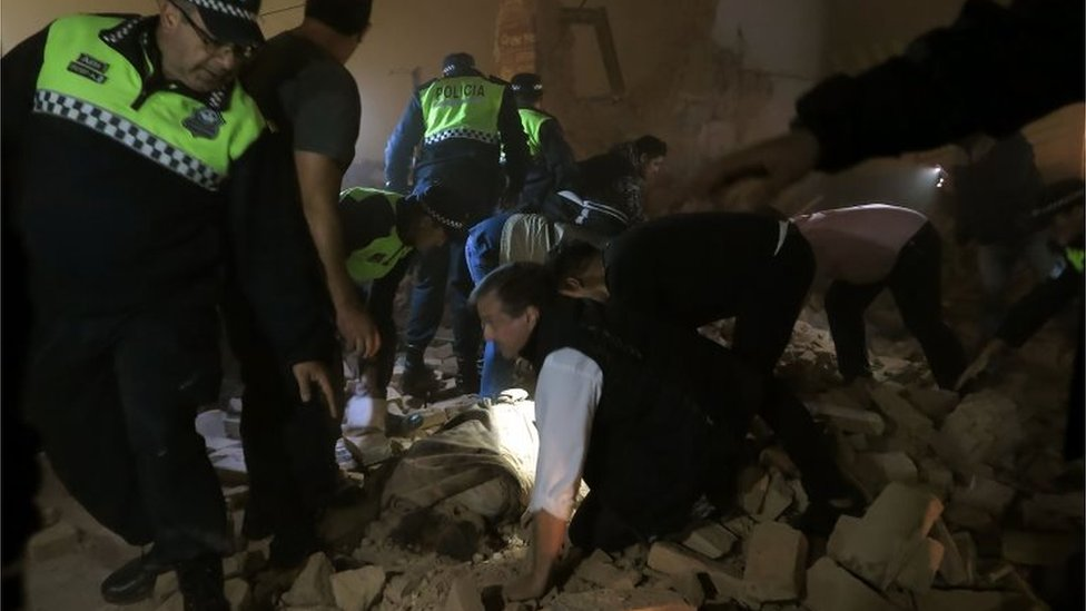 Police and passers-by look for victims in the rubble, minutes after the collapse of the old Parravicini movie theatre building, in Tucuman, Argentina on May 23, 2018.