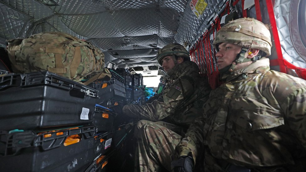 Soldiers inside a chinook taking supplies to Cumbria