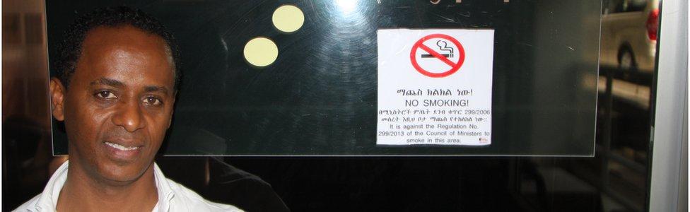 Stockholm Elegance bar owner Amare Reda stands beside a no-smoking sign.