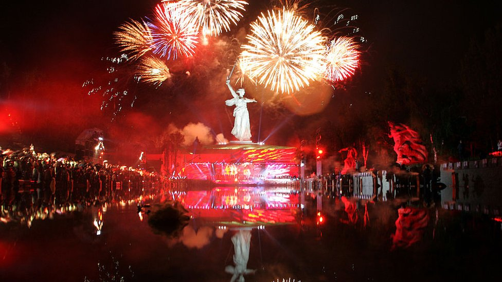 People watch fireworks explode over The Motherland Calls statue in Volgograd, Russia