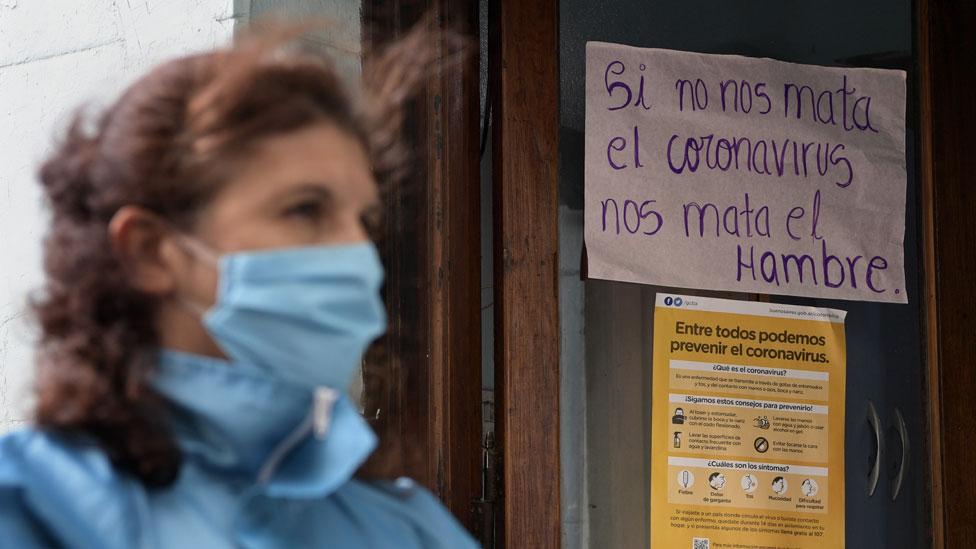 """Una mujer en Buenos Aires usando un tapabocas frente a un cartel que dice: """"Si no nos mata el coronavirus, nos mata el hambre""""."""