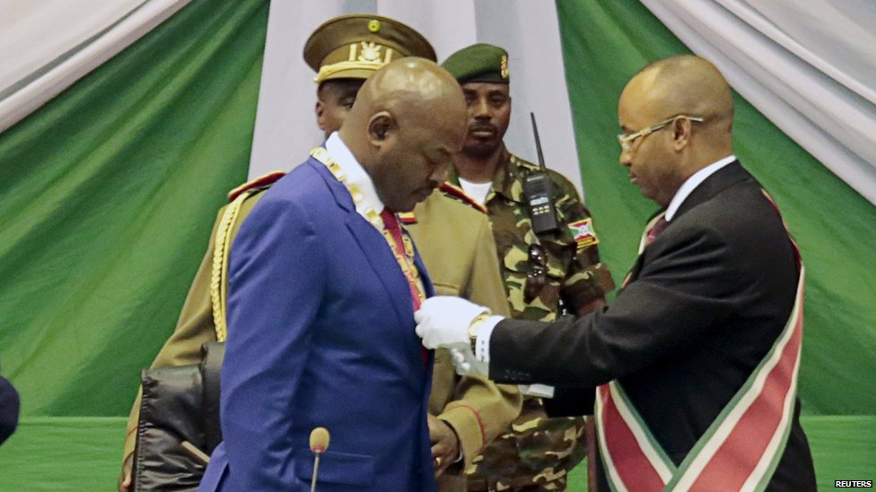 Pierre Nkurunziza (L) receives a symbolic chain at the Congress Palace in Kigobe district, Bujumbura, August 20, 2015.