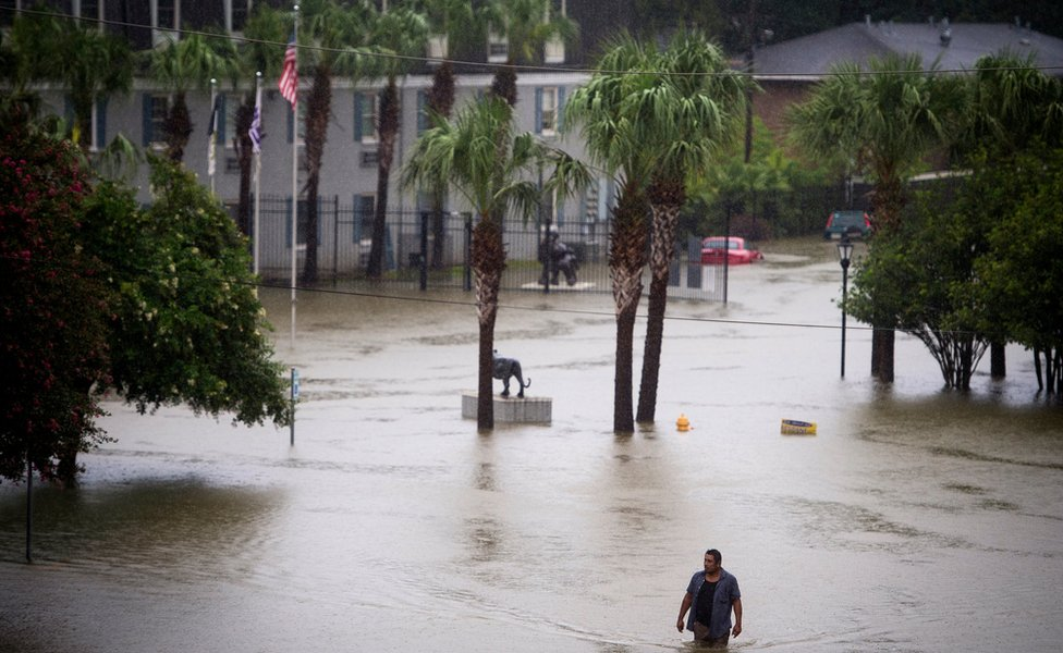 A resident wades through flood water at Tiger Manor Apartments by the North Gates of LSU, Saturday, Aug. 13, 2016, in Baton Rouge, La.