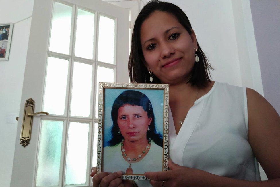 Isamar con un retrato de su madre