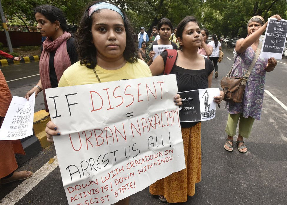 "A woman at a protest holding a poster saying, ""If dissent = urban naxalism, arrest us all"""