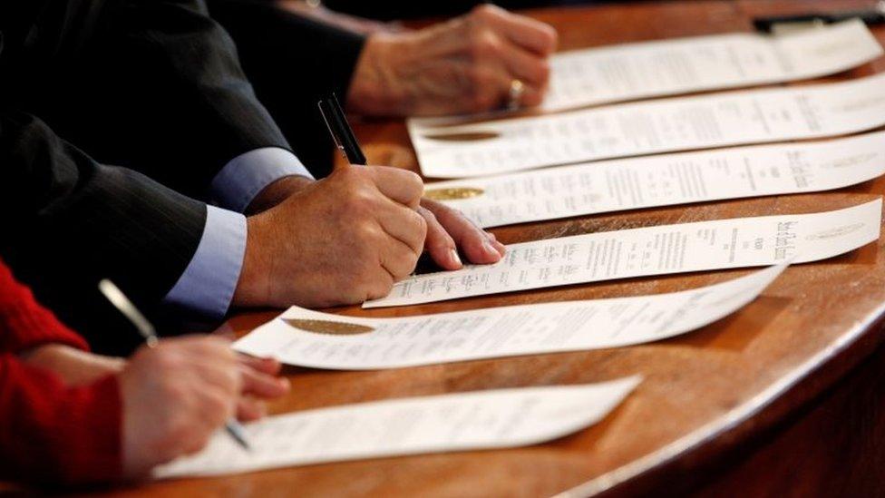 Electores del Colegio Electoral firmando actas