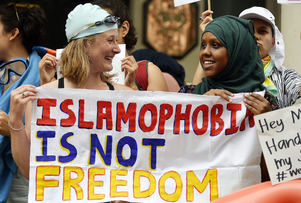 Two women - one white and in a swimming cap and goggles, the other black and wearing hijab - hold a sign saying 'Islamophobia is not freedom'