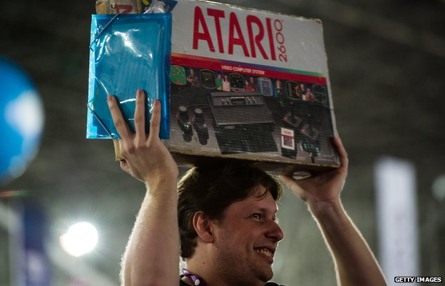 Man holding Atari 2600 box