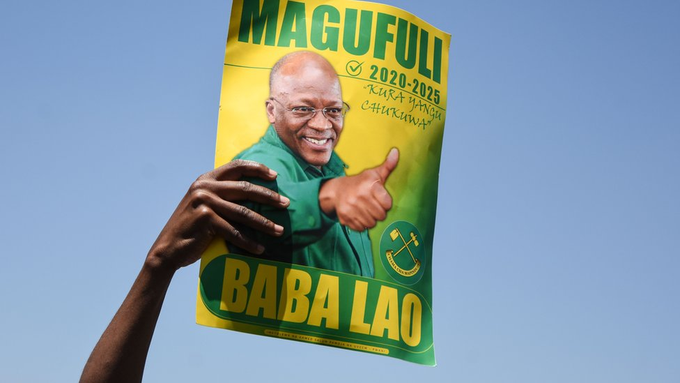 A supporter of President John Magufuli holds a sign during the official launch of the party's campaign for the October general election