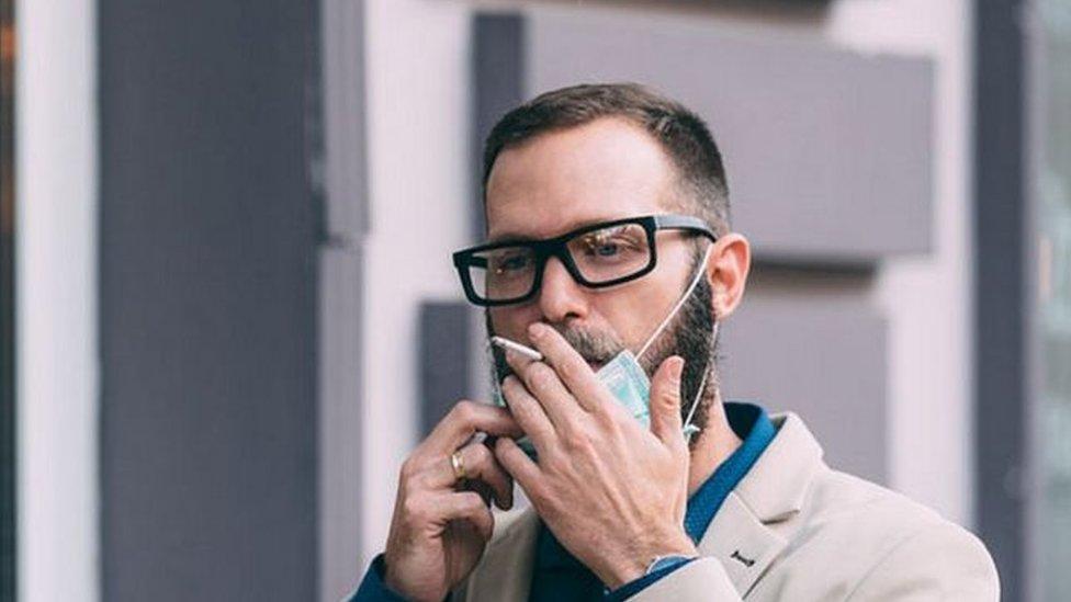 رجل يدخن مرتديا كمامة