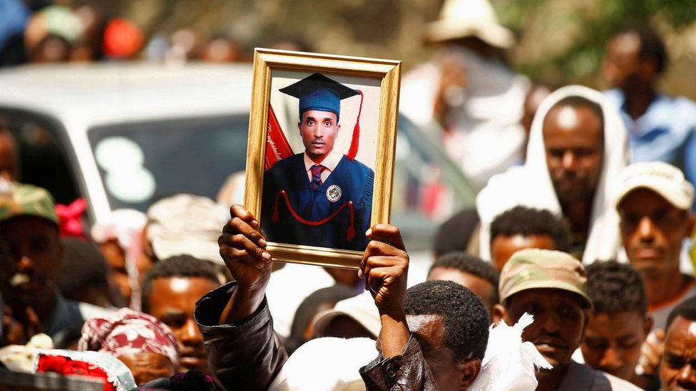 A man at a funeral holds up the portrait of Tesfu Tadese Biru in a crowd of mourners