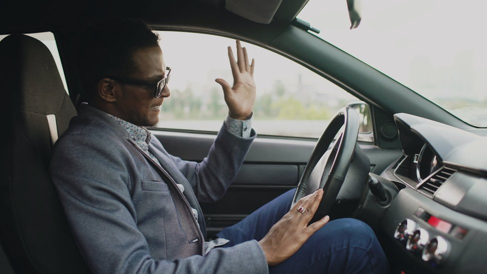 A man at the wheel of a car, visibly annoyed with the traffic - he's gesticulating, and it looks like he might be swearing