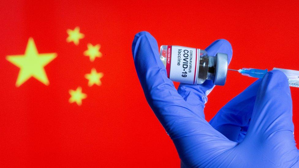 設計圖片:一位女護士在中國國旗前預備新冠疫苗針劑