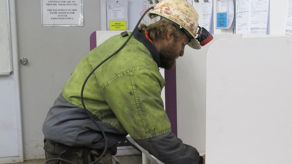 A miner votes in a polling booth