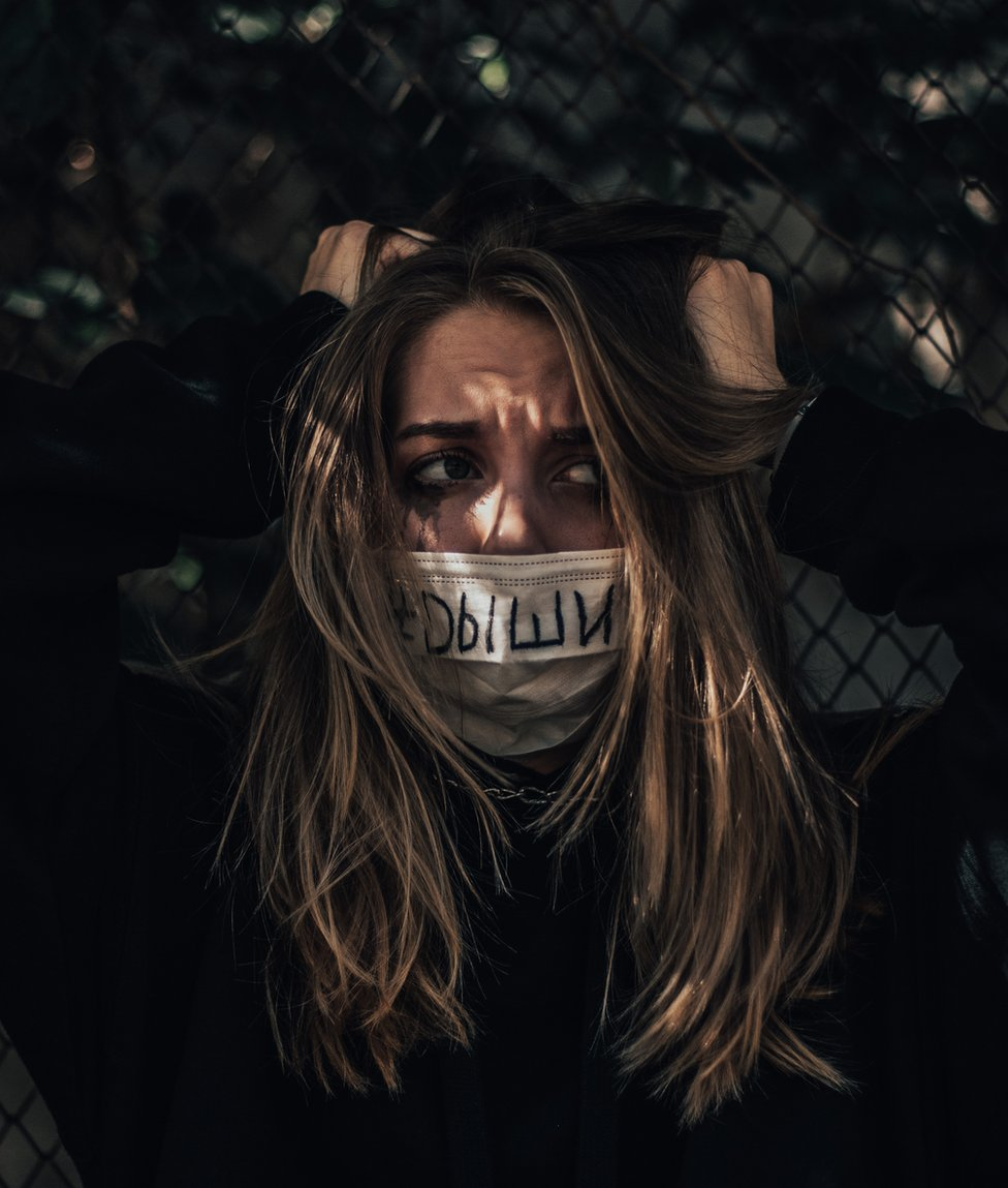 Image of a woman with a mask which has 'breathe' written on it in Russian