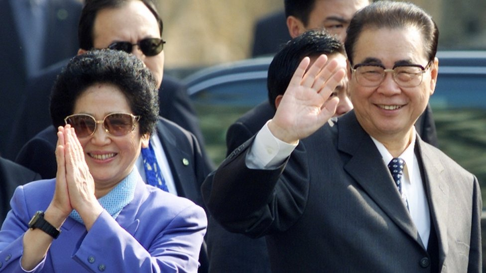 Li Peng and his wife Zhu Lin wave to crowds