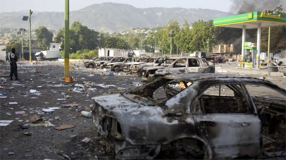 Burned cars sit parked outside the Delimart supermarket complex, near a gas station, after two days of protests against a planned hike in fuel prices in Port-au-Prince, Haiti, Sunday, July 8, 2018.