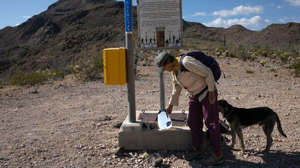 """Activista de """"No More Deaths"""" dejando un galón de agua en el desierto."""