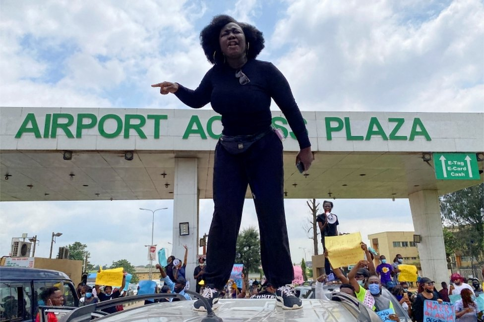 A protester stands on top of a vehicle and shouts slogans as others carry banners while blocking a road leading to the airport, during a demonstration against alleged police brutality, in Lagos, Nigeria, October 12, 2020.