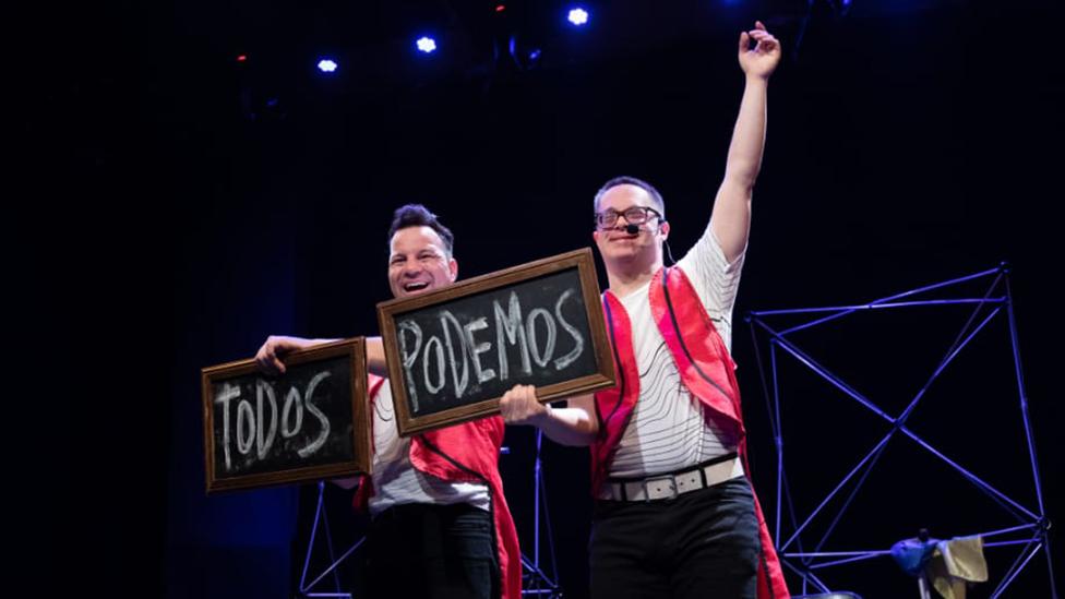 """MagOmi y MagoAle en una presentación de """"Magia Inclusiva"""" con carteles que dicen """"Todos Podemos"""""""