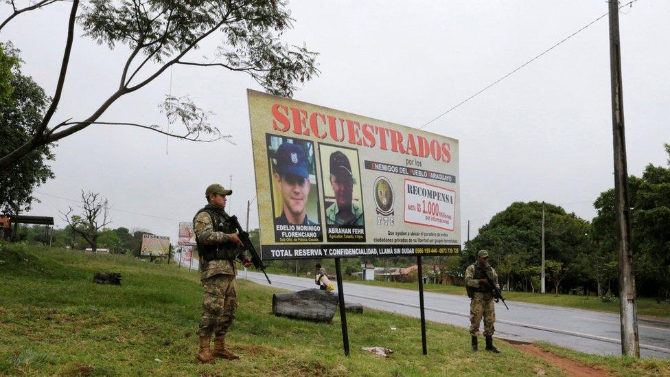 Soldados patrullan frente a un cartel de secuestro.