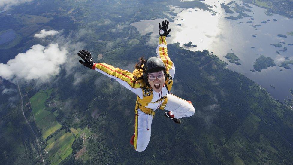 Mujer con paracaídas saltando de un avión