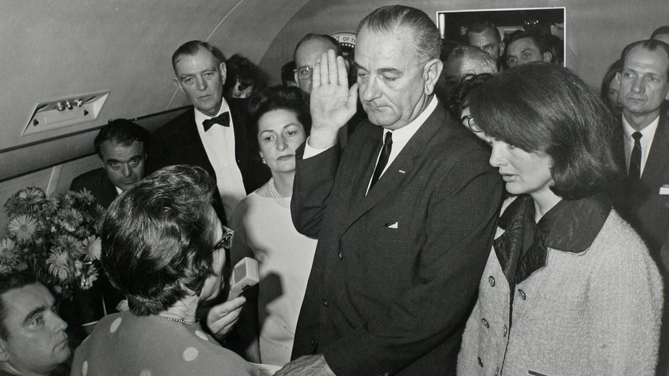 Vice-President Lyndon Baines Johnson (C) is sworn in as JFK's stunned widow stands by just two hours after he was shot