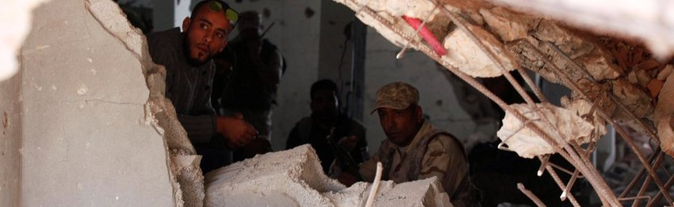 Fighters of Libyan forces allied with the U.N.-backed government sit in a damaged house as they secure the last few buildings where Islamic State militants had been making a final stand